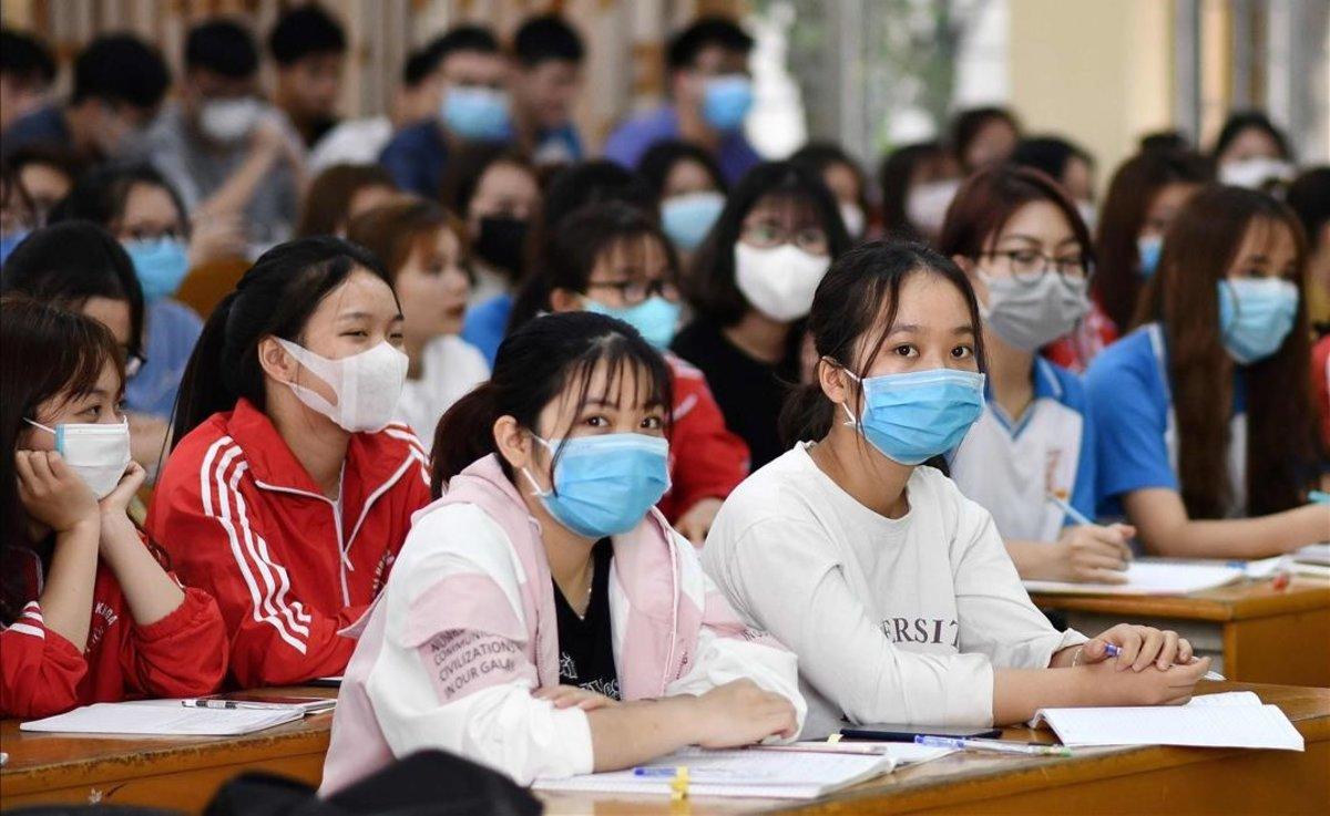 Estudiantes protegidos con mascarillas ante la expansión del coronavirus en la Universidad de Hanoi.