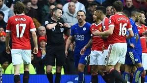 El árbitro inglés en medio de una protesta en el partido Manchester United-leicester.