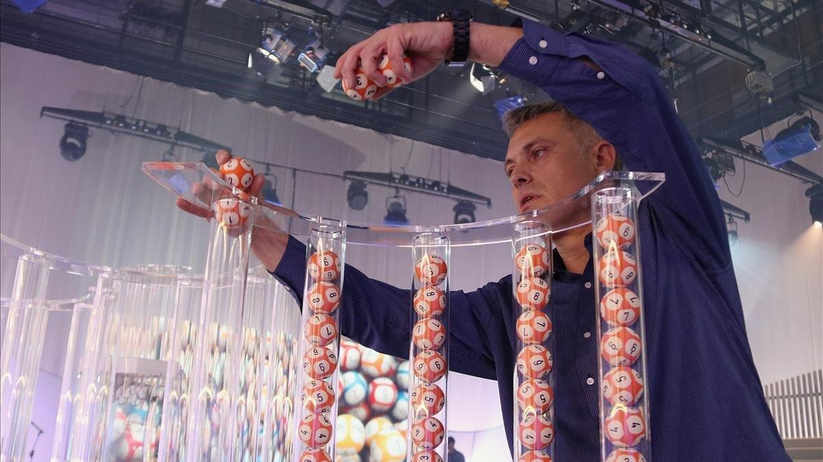 Un operario coloca las bolas en los tubos para el sorteo de la Grossa de Cap d'Any.