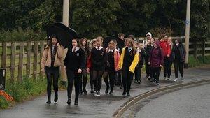 Un grupo de estudiantes escoceses llegan a su escuela, este martes, en su primer día de colegio tras los cinco meses de parón por la pandemia.