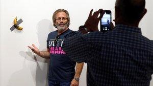 Un hombre se retrata junto a la obra del artista italiano Maurizio Cattelan.