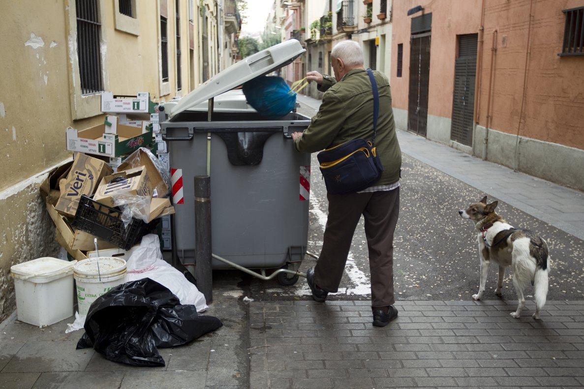 Un hombre tirando la basura al contenedor.