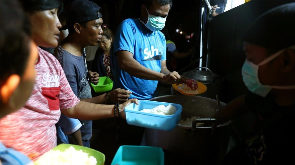 Afectados del terremoto y el tsumani reciben comida en un centro de atención en Palu.