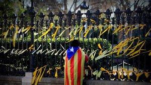 Un joven con la bandera indepentista anudada a su espalda coloca lazos amarillos en la verja que rodea el Parc de la Ciutadella, el pasado enero.