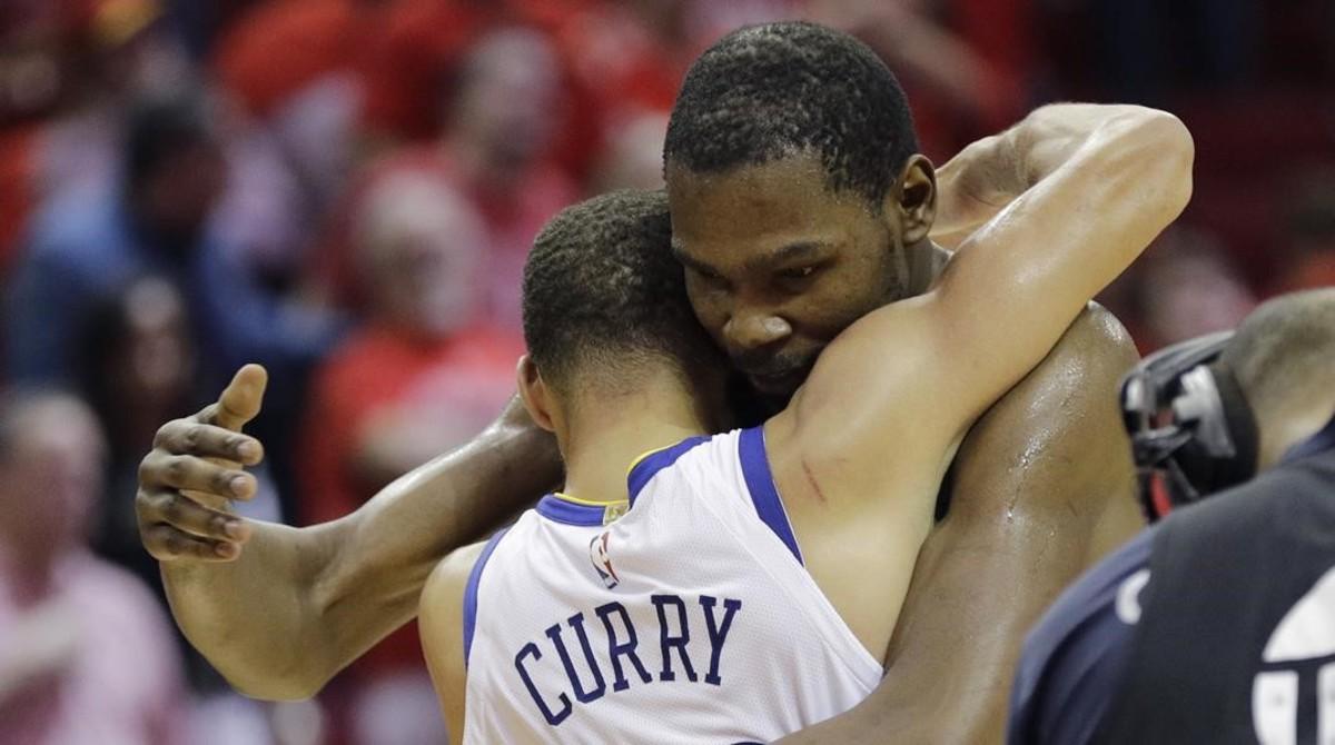 Kevin Durantabraza a Stephen Curry (de espaldas) después de que los Warriors derrotaran a los Rockets.