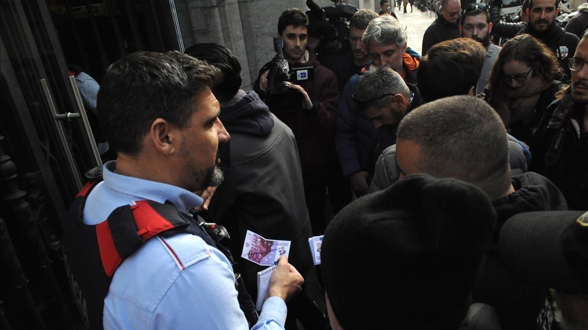 Los taxistas dan un billete falso de 500 euros a un mosso, durante su protesta en la sede de la Autoritat Catalana de la Competència.