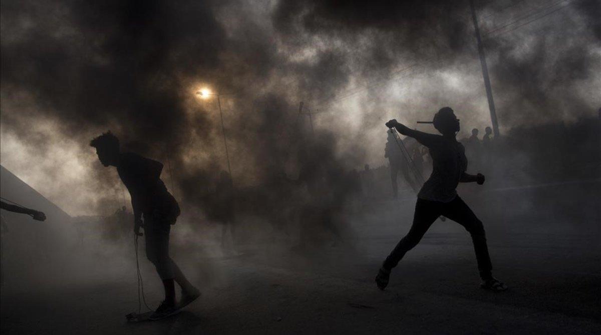 Manifestantes palestinos lanzan piedras contra soldados israelís en la frontera de Gaza con Israel.