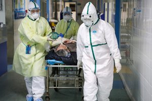 Medical workers in protective suits move a patient at an isolated ward of a hospital in Caidian district following an outbreak of the novel coronavirus in Wuhan, Hubei province, China February 6, 2020. Picture taken February 6, 2020. China Daily via REUTERS ATTENTION EDITORS - THIS IMAGE WAS PROVIDED BY A THIRD PARTY. CHINA OUT.
