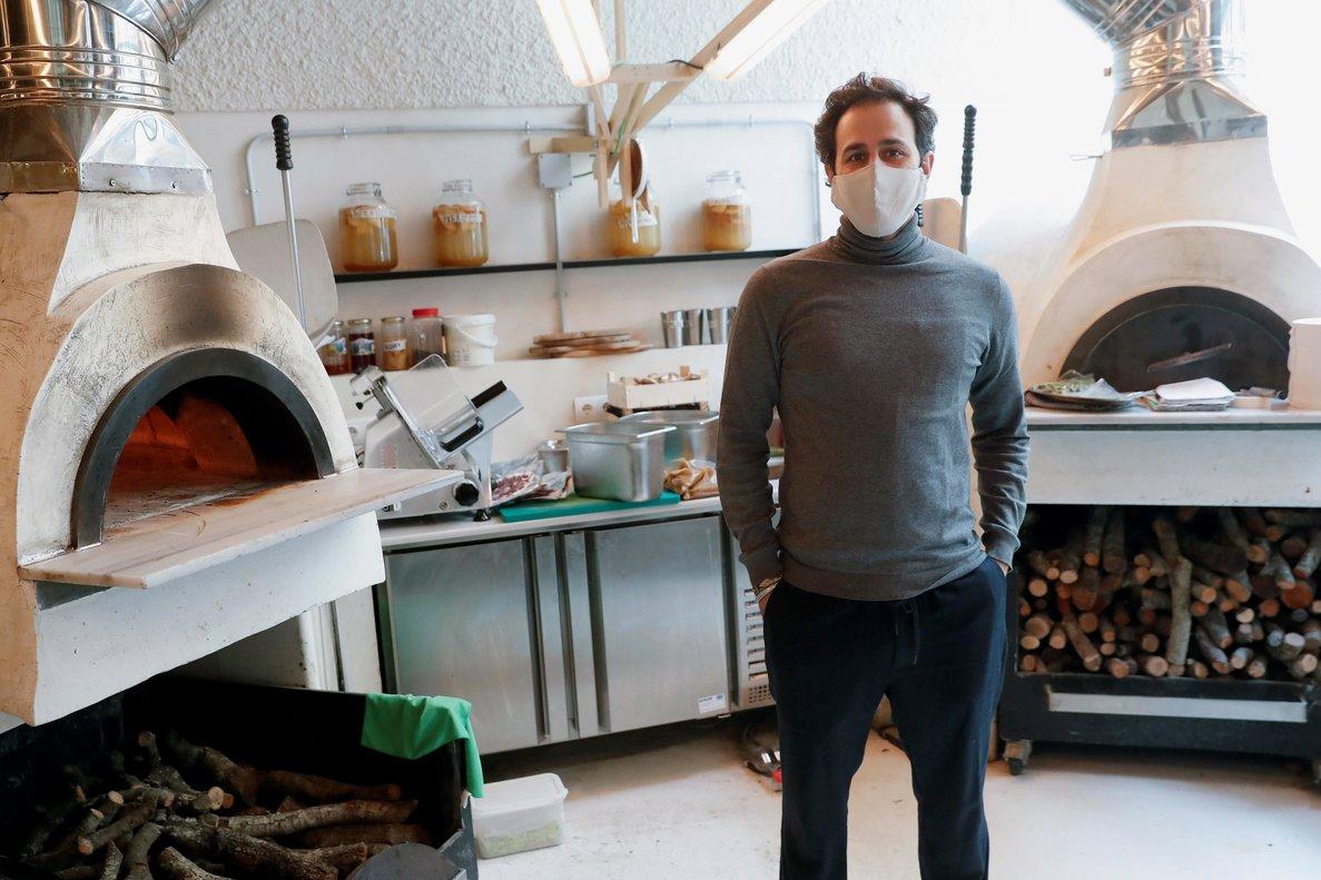 El coofundador de MO de Movimiento, Felipe Turell, junto a los hornos de pizza del restaurante, que también calientan el local.