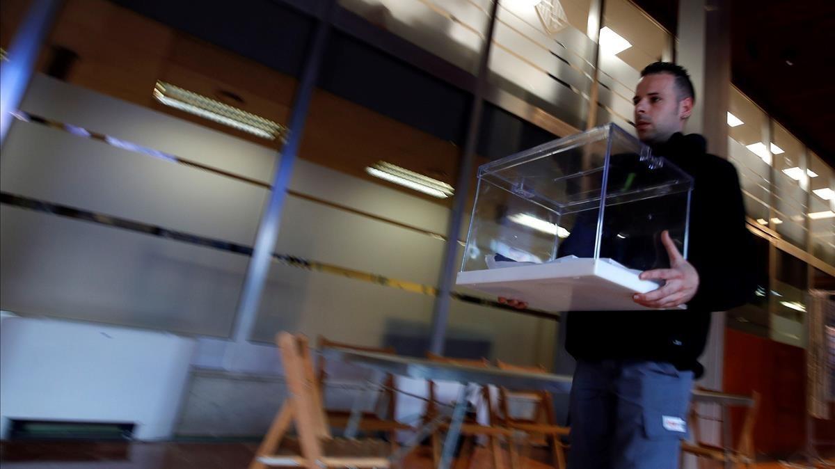 Un operario traslada una urna en el Ayuntamiento de Barcelona, que es colegio electoral.