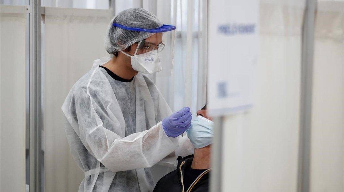 Un sanitario realiza una prueba PCR auna persona posiblemente contagiada porCovid-19.