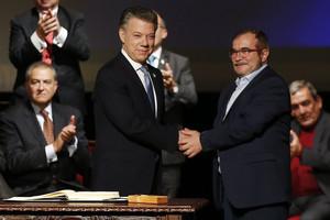 Santos (izquierda) y Rodrigo Londoño, alias 'Timochenko', se dan la mano tras firmar el nuevo acuerdo, en Bogotá, este jueves.