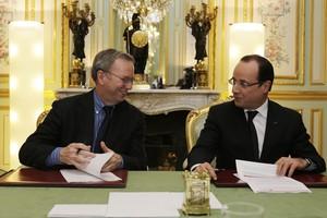 Schmidt (izquierda) y Hollande firman el acuerdo, en París.