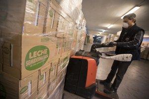 Un voluntario descarga una donación de la empresa Mercadona que ha realizado a El Banc dels Aliments esta mañana en el decimoctavo día del estado de alarma decretado por el gobierno español debido al Coronavirus Foto: Marta Pérez