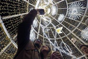 Transeúntes ante las luces de Navidad en Málaga.