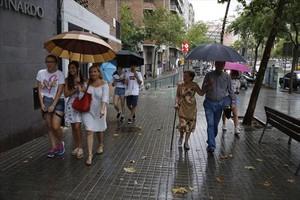 Transeúntes con paraguasen la Ronda de Guinardó de Barcelona, en una imagen de archivo.