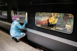 Una doctora mira a un paciente trasladado en tren de París a la Bretaña, este miércoles.