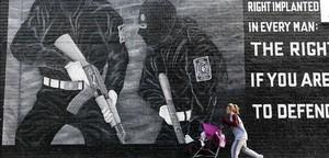 Una dona amb un cotxet de criatura passa davant d'un mural de paramilitars unionistes, a l'est de Belfast, aquest dimecres.