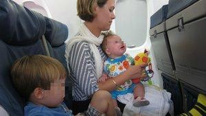 Una madre con sus hijos, viaja en avión.