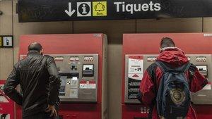 Usuarios del metro de Barcelona comprando billetes, este miércoles.