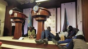 Varios periodistas se tiran al suelo al oír los tiroteos en el exterior del palacio presidencial, en Yuba, este viernes.