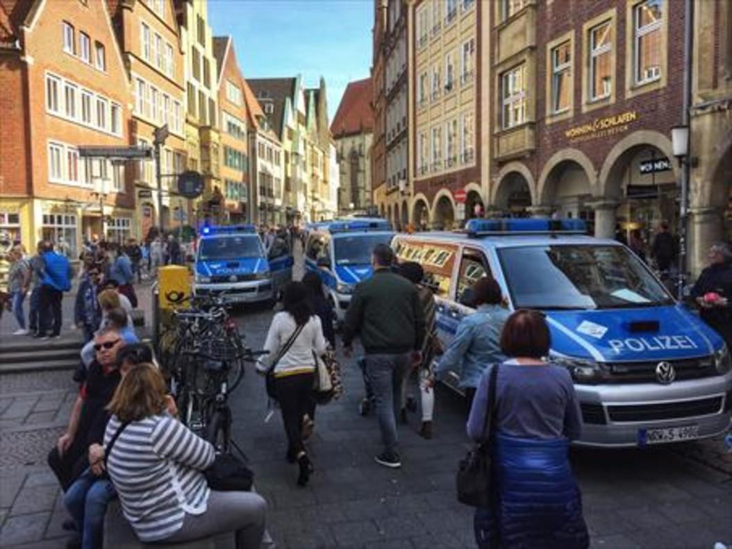 Vecinos y turistas circulan por el centro de Münster, entre furgonetas de la policía, tras el atropello de ayer.