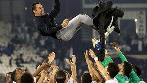 Xavi, manteado por sus jugadores después de ganar la final de la Qatar Cup.