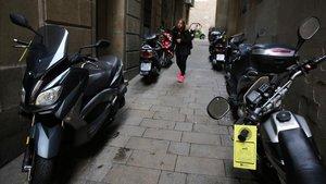 Avisos de prohibición de estacionar, con amenaza de retirada con grúa, en motos aparcadas este martes por la tarde en la calle de Arlet, cerca de la plaza de Sant Jaume de Barcelona.