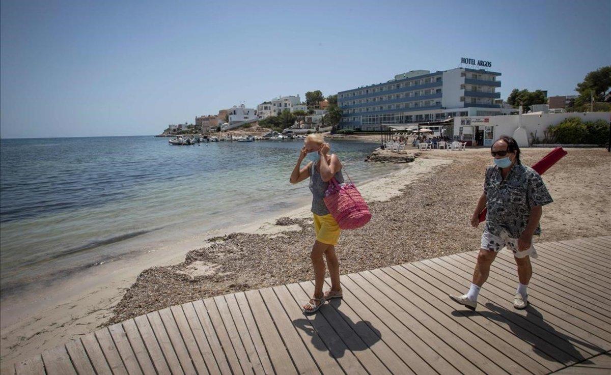 Turistas con mascarilla llegan a la playa de Talamanca, en Ibiza.