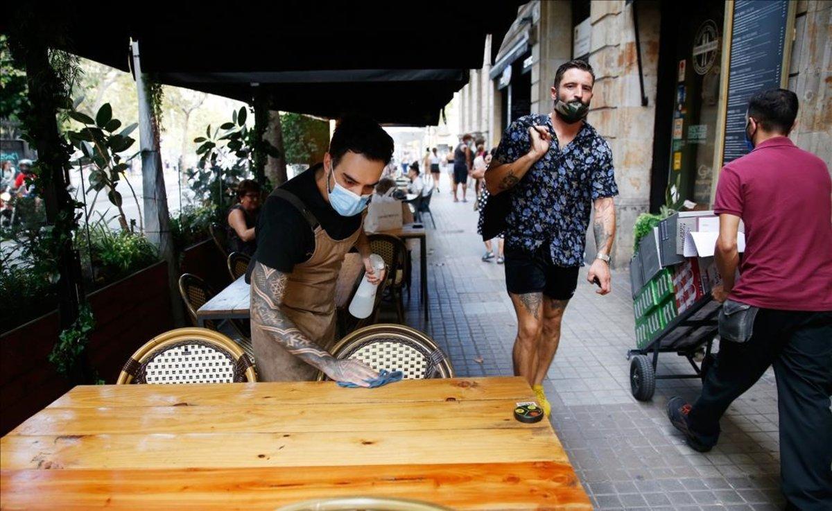 Un trabajador de un bar de Barcelona limpia una mesa de la terraza del local.