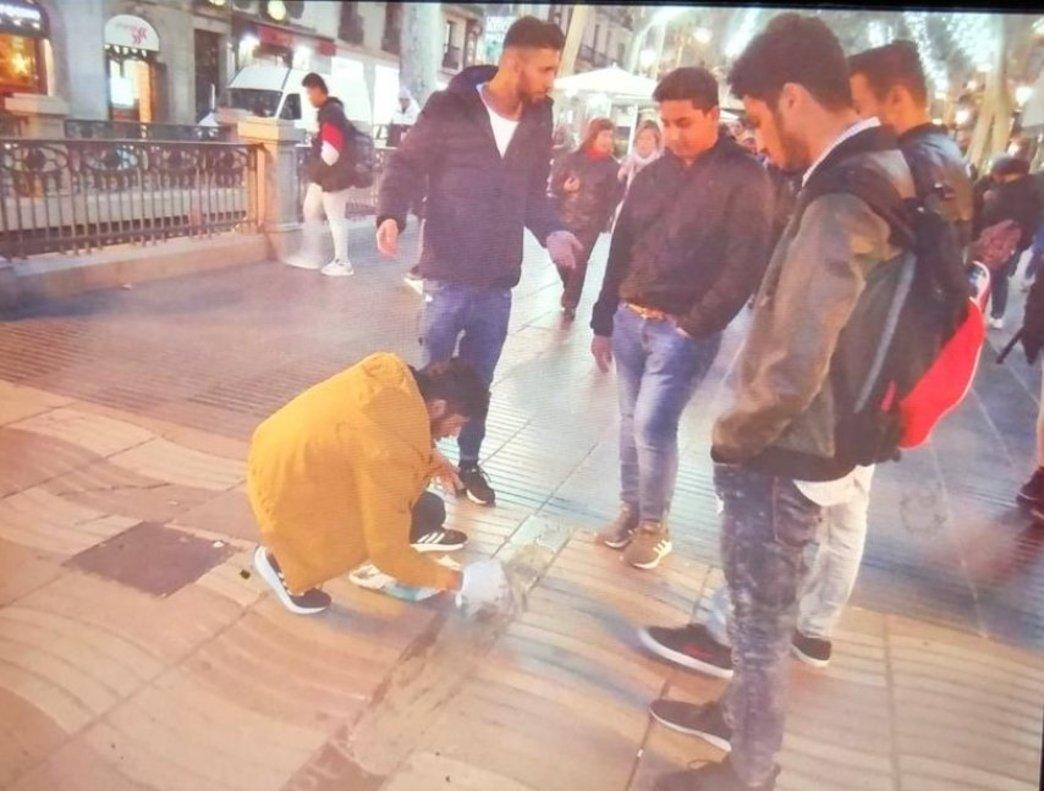 Momento en que unos hombres tapan con cemento la inscripción en árabe del memorial por las víctimas del 17-A.