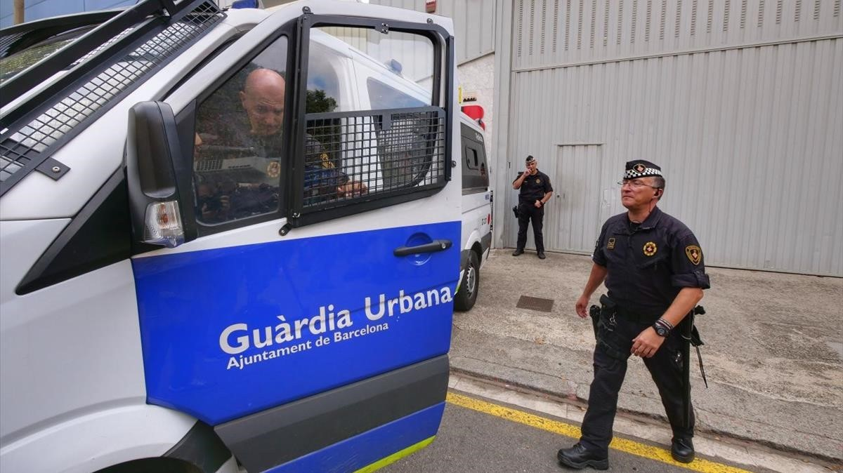 Un agente ante un coche de la Guardia Urbana.