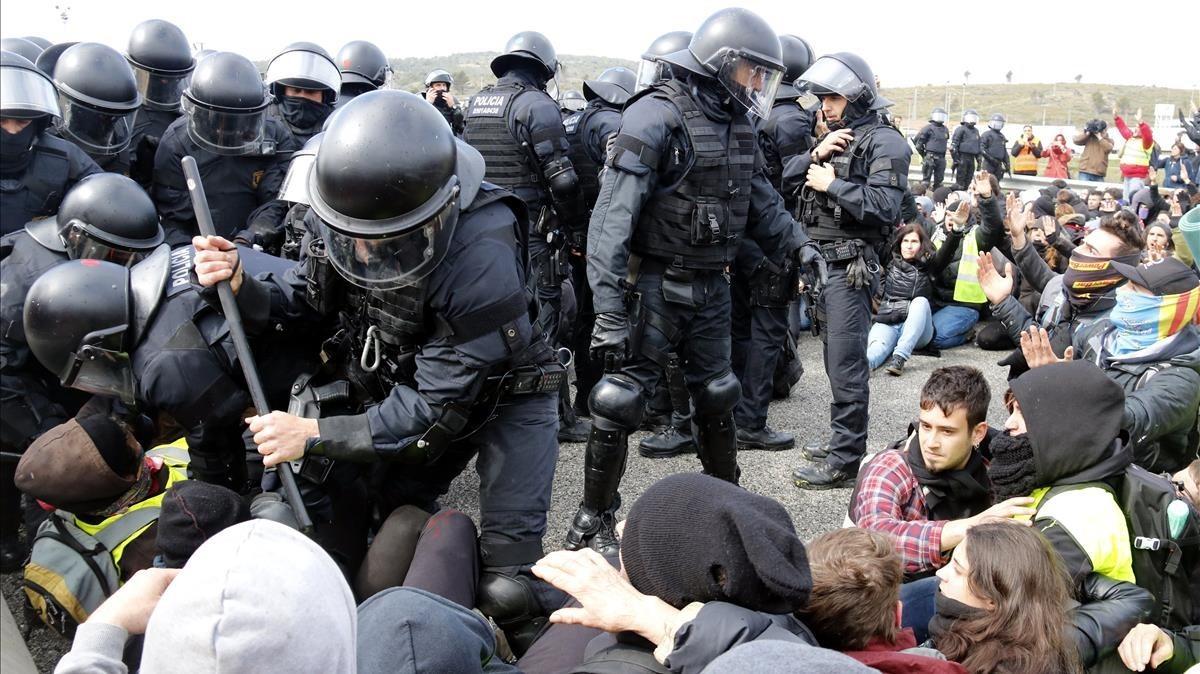 Agentes de los Mossos desalojan por la fuerza la AP-7 a la altura de Figueres.