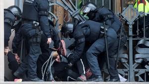 Agentes de los Mossos enfrentándose a uno de los manifestantes encadenados.