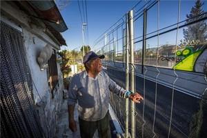 Antonio, en su casa de Murcia junto a una valla y el muro por el AVE.