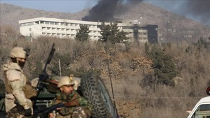 Soldados afganos montan guardia en los accesos alhotel asaltado del que sale una columna de humo.