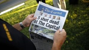 Un hombre sustenta le edición de este viernes del diario Capital Gazette