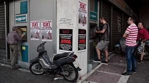 Colas ante cajeros en Atenas (Grecia), con carteles a favor del 'no' en el referéndum.
