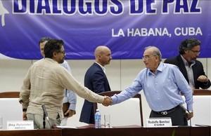 El comandante de las FARC y líder del equipo negociador de paz Luciano Marin 'Ivan Marquez' estrecha la mano del jefe negociador del Gobierno colombiano Humberto de la Calle, el viernes.