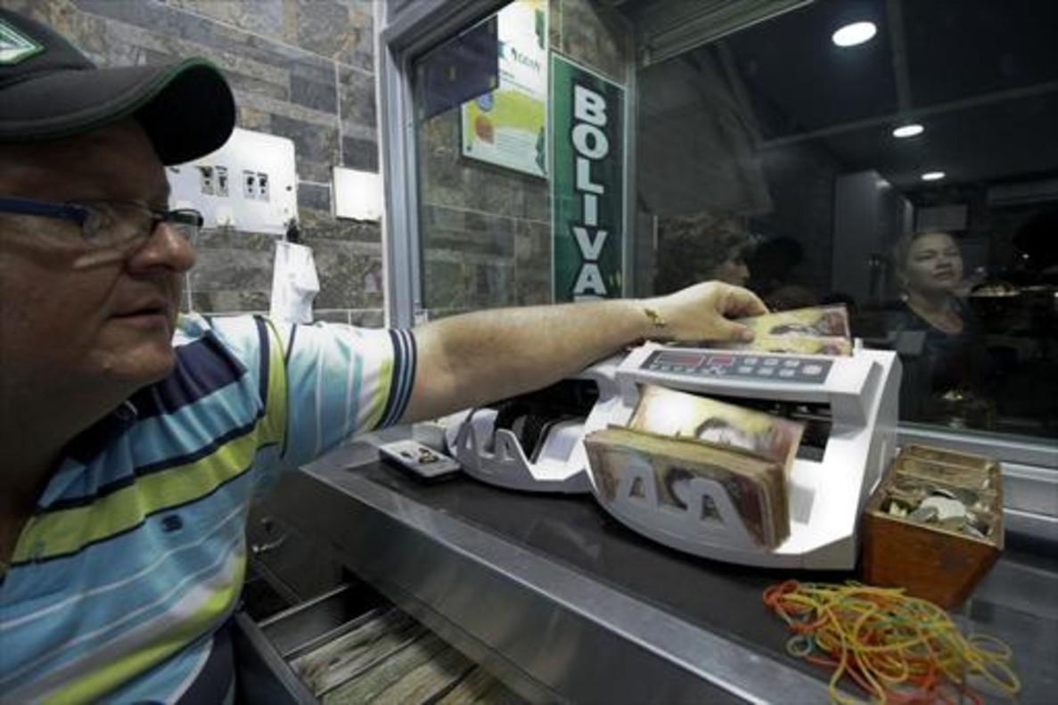Un empleado de una oficina de cambio colombiana, en la frontera con Venezuela, cuenta billetes de 100 bolívares.