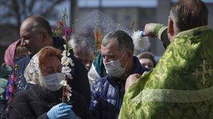 Fieles con máscara en una ceremonia de pascua ortodoxa en Minsk.