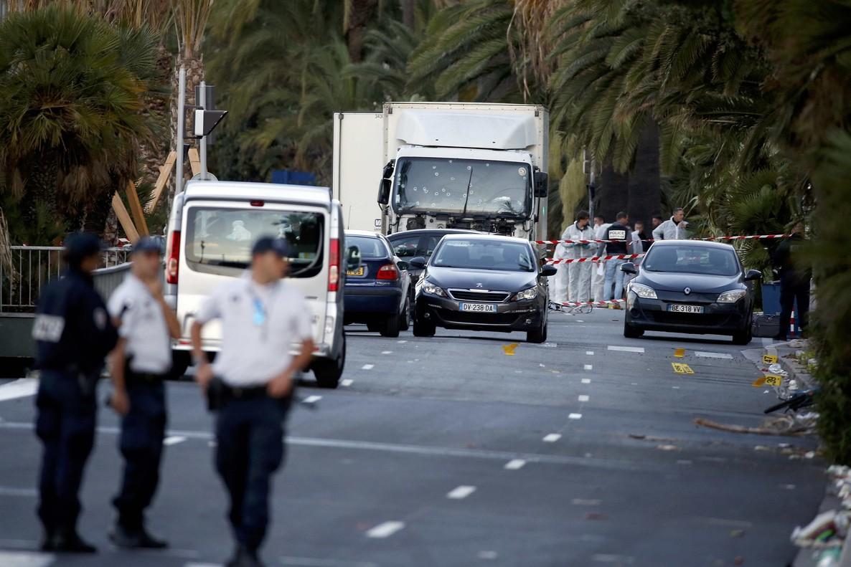 Gendarmes continúan la investigación de la masacre en Niza, donde un camión (al fondo) ha arrollado a la multitud y causando más de 80 muertos.