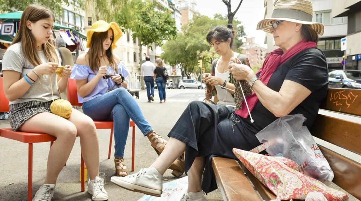 Un grupo de mujeres haciendo punto en la calle el Día Mundial de Tejer en Público, en la Via Augusta, frente al Club de la Aguja.