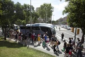 Grupos de turistas excursionistas, que visitan Barcelona sin pernoctar, se dirigen a los autocares aparcados en la zona de Diagonal-Aragó después de ver el templo de la Sagrada Família.