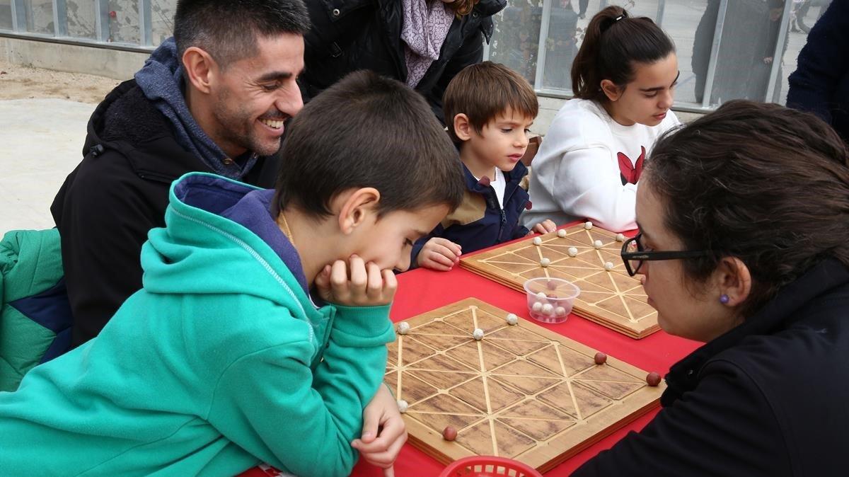 Niños y adultos se divierten con un juego de mesa.