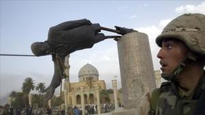 El marine Kirk Dalrymple mira como cae la estatua de Sadam Husein el día de la caída de Bagdad.