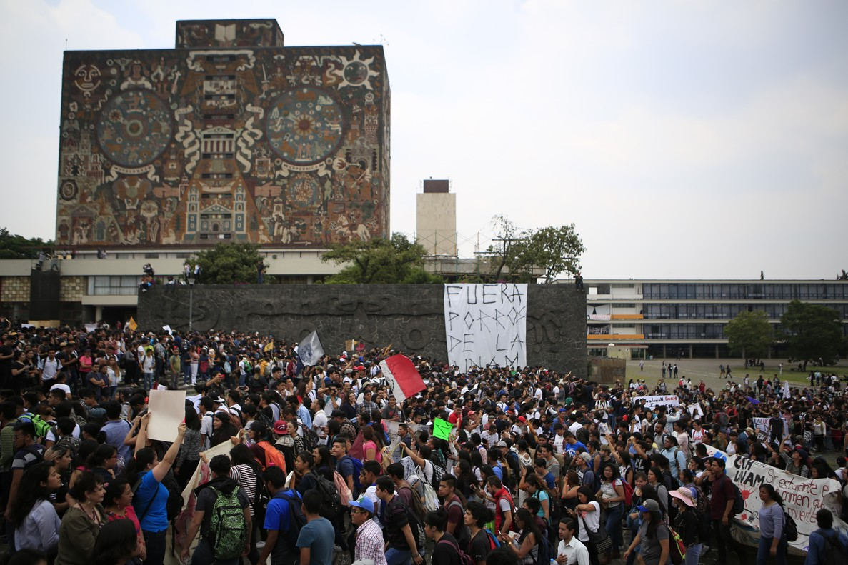 Protestors march past a banner reading in Spanish  Porros get out of UNAM   outside the Rectoria at Mexico s National Autonomous University  UNAM   as thousands protested demanding an end to violent by groups of thugs known as  porros   at the University s main campus in Mexico City.