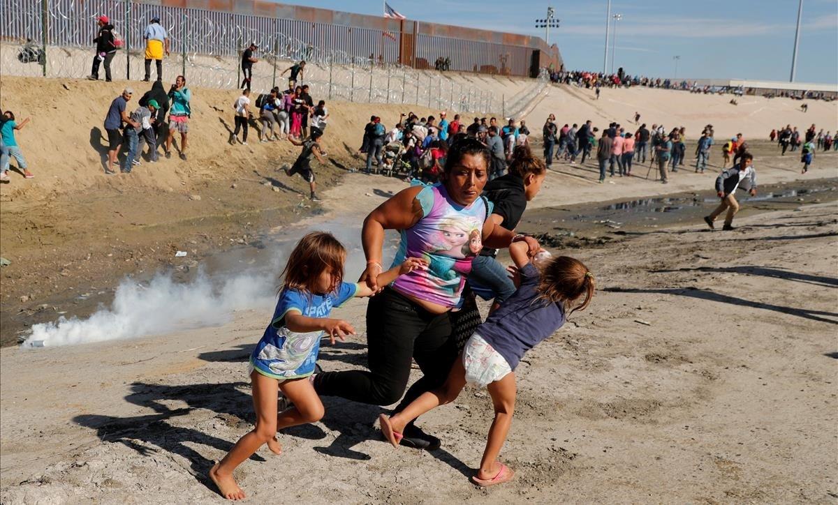 Migranteshuyen de los gases lacrimógenos en el muro entre EEEUU y México, en Tijiuana