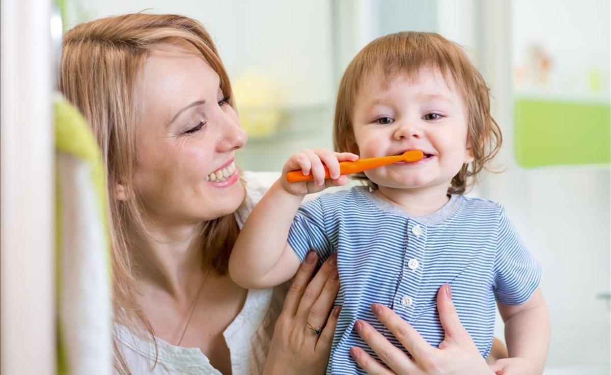 Un niño se lava los dientes de forma autónoma con la ayuda de su madre.