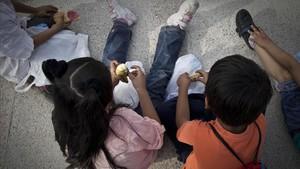 Unos niños, en la calle, a la hora de la merienda.